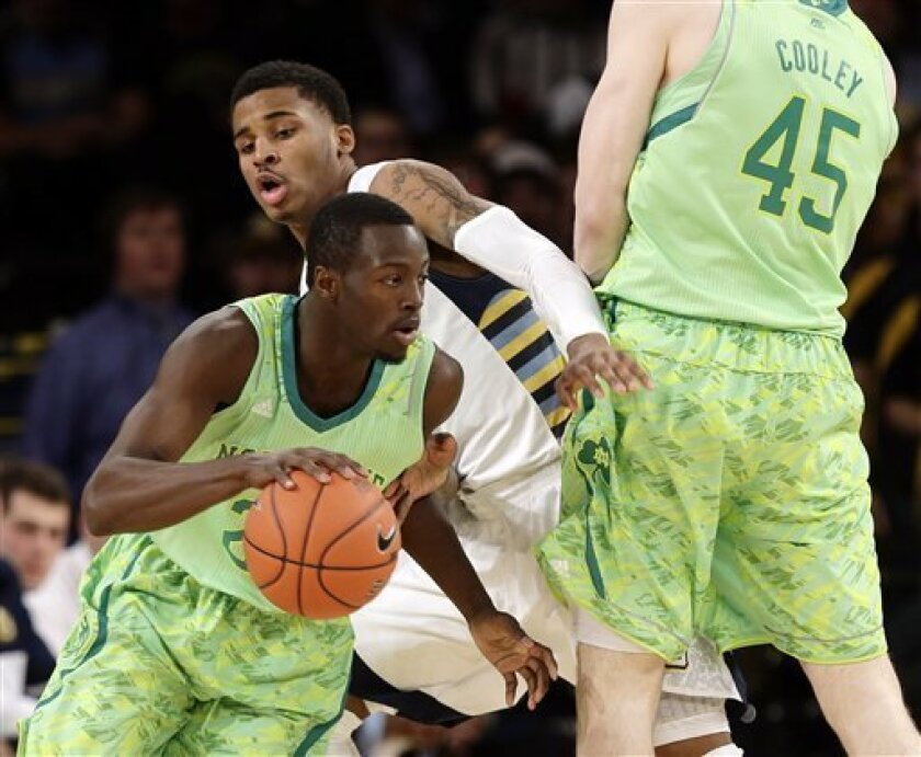 Marquette's Vander Blue, center, chases Notre Dame's Jerian Grant, left, around a pick set by Jack Cooley, right, during the first half of an NCAA college basketball game at the Big East Conference tournament, Thursday, March 14, 2013, in New York. (AP Photo/Frank Franklin II)