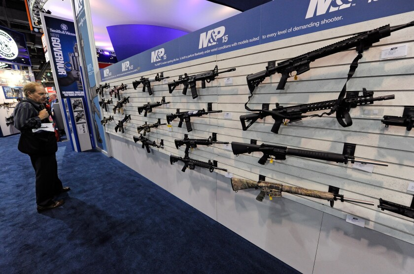 An attendee looks at Smith & Wesson M&P15 rifles at the Smith & Wesson booth at a Vegas trade show