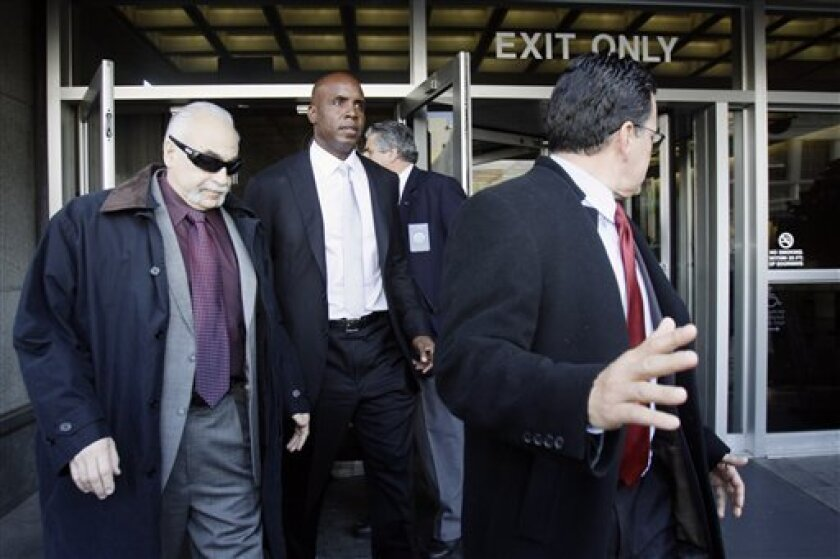 Barry Bonds, center, leaves the federal courthouse after the first day of his trial, Monday, March 21, 2011, in San Francisco. Bonds played for the San Francisco Giants baseball team and hasn't played since his 2007 indictment. (AP Photo/Marcio Jose Sanchez)