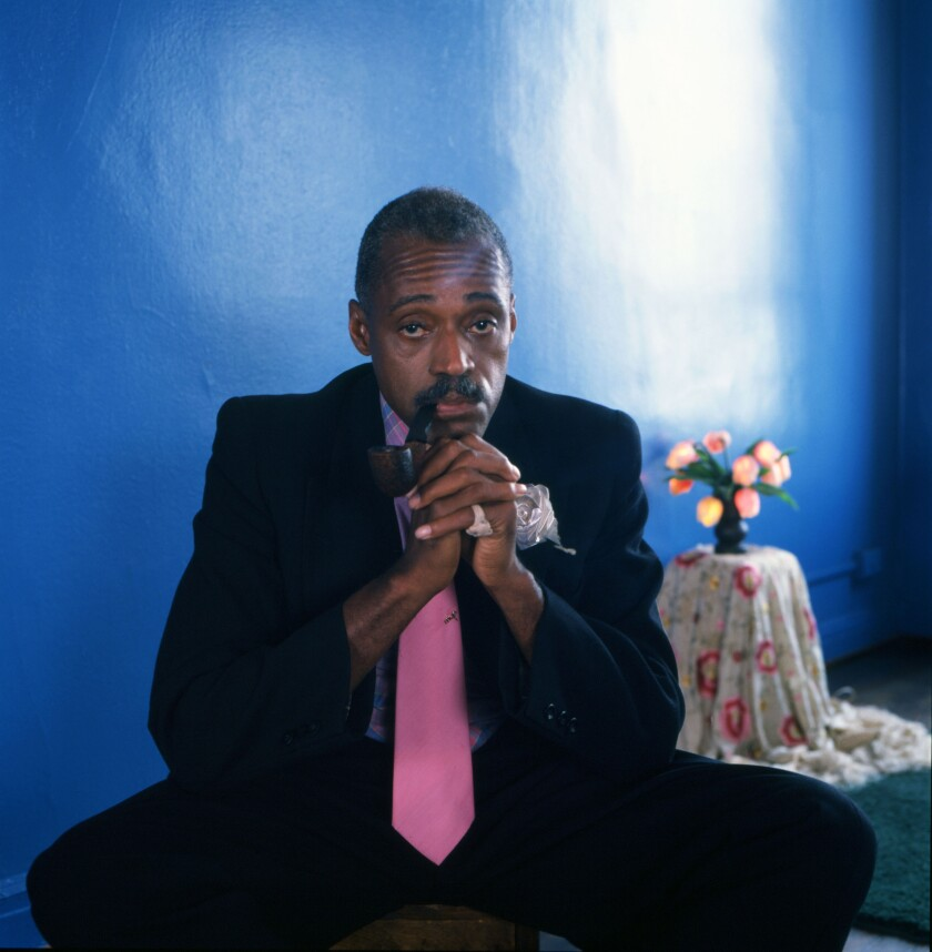 A man wears a suit and a pink tie