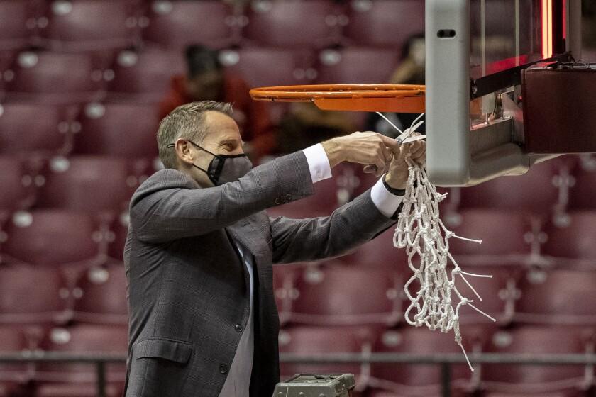 Alabama head coach Nate Oats cuts the net after an NCAA college basketball game against Auburn, Tuesday, March 2, 2021, in Tuscaloosa, Ala. Alabama won the regular season Southeastern Conference championship. (AP Photo/Vasha Hunt)