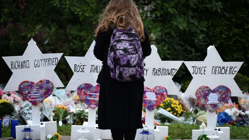 In Pittsburgh, a woman stands before a memorial to the victims of the Oct. 27, 2018, mass shooting at the Tree of Life synagogue.
