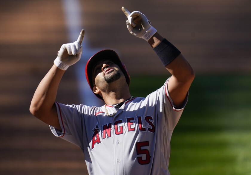 Angels slugger Albert Pujols points skyward as he crosses the plate after hitting a home run.