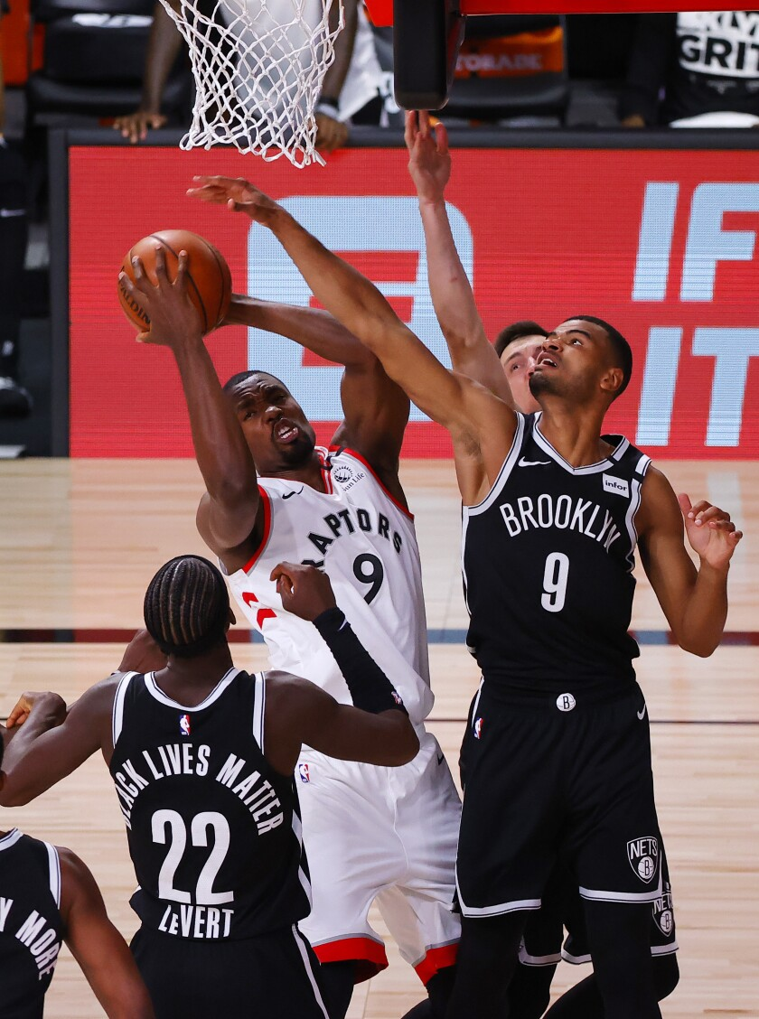 Toronto Raptors' Serge Ibaka, top left, grabs a rebound against Brooklyn Nets' Timothe Luwawu-Cabarrot, right, and Caris LeVert (22) during the third quarter of Game 1 of an NBA basketball first-round playoff series, Monday, Aug. 17, 2020, in Lake Buena Vista, Fla. (Kevin C. Cox/Pool Photo via AP)