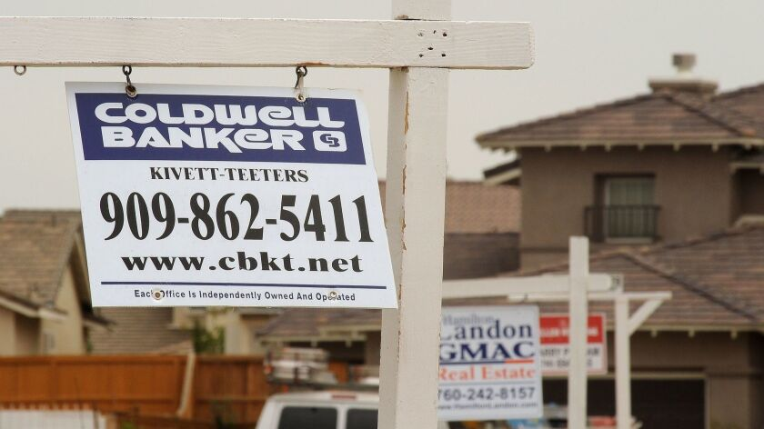 For-sale signs line a residential street in Adelanto. Last month, state lawmakers sought to block a court ruling to repay $331 million from a national settlement of claims during the mortgage and foreclosure crisis.