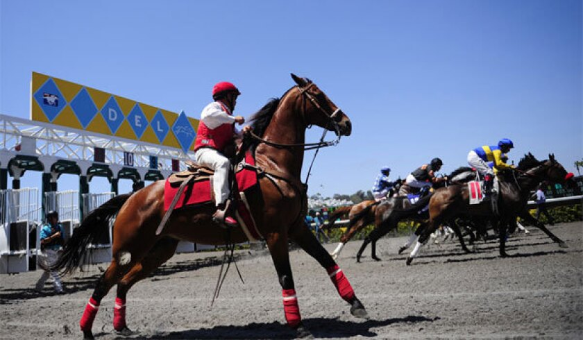 An outrider watches as horses leave the gate during the opening day of horse racing at Del Mar in 2018.