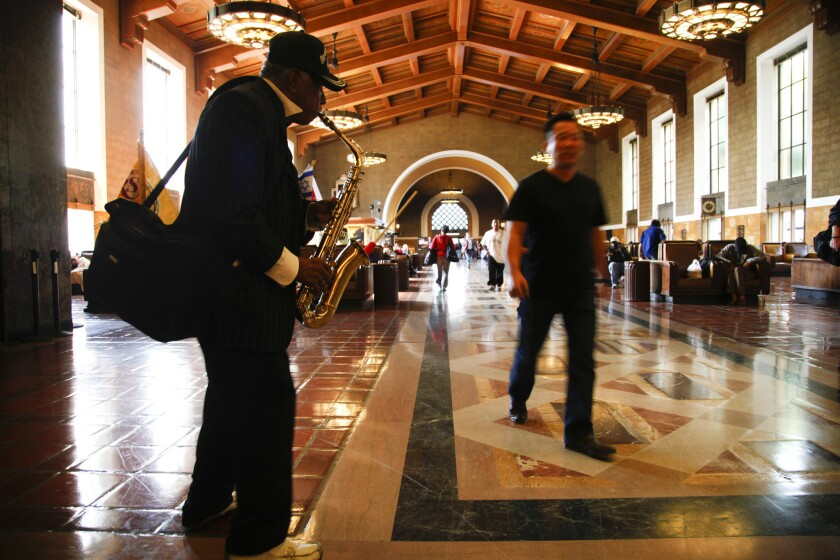 Retired bus driver Ruben Rodriquez plays the saxophone and sometimes plays his guitar for travelers running through Union Station in Los Angeles.