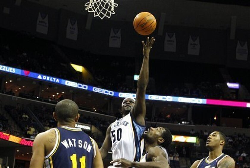 Memphis Grizzlies' Zach Randolph, top, puts up a shot over Utah Jazz's Earl Watson, left, and Derrick Favors, right, as teammate Tony Allen, second right, looks on during the first half of an NBA basketball game in Memphis, Tenn., Monday, March 21, 2011. (AP Photo/Mark Weber)