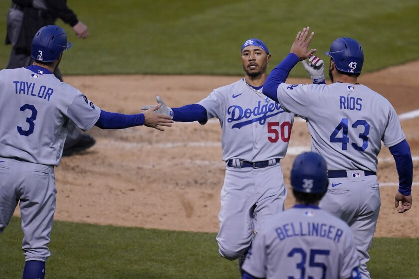 Los Angeles Dodgers' Chris Taylor (3) celebrates with Mookie Betts (50) and Edwin Rios (43) after all scored on a three-run double hit by Corey Seager during the second inning of a baseball game against the Oakland Athletics in Oakland, Calif., Monday, April 5, 2021. (AP Photo/Jeff Chiu)