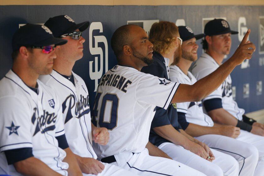 The Padres' Odrisamer Despaigne tosses sunflower seed shells on to teammates while in the dugout.