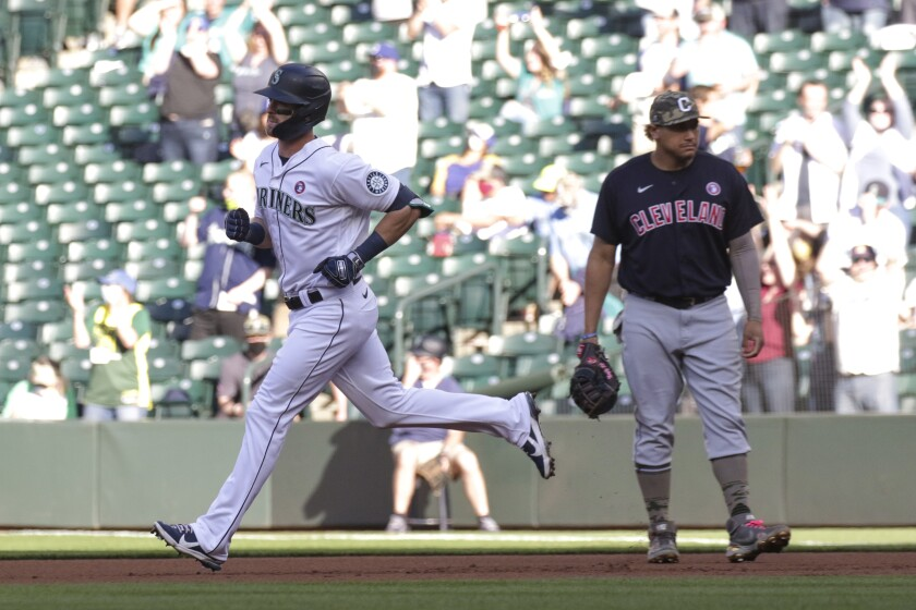 Seattle Mariners' Mitch Haniger runs past Cleveland Indians first baseman Josh Naylor following a solo home run during the first inning of a baseball game Saturday, May 15, 2021, in Seattle. (AP Photo/Jason Redmond)