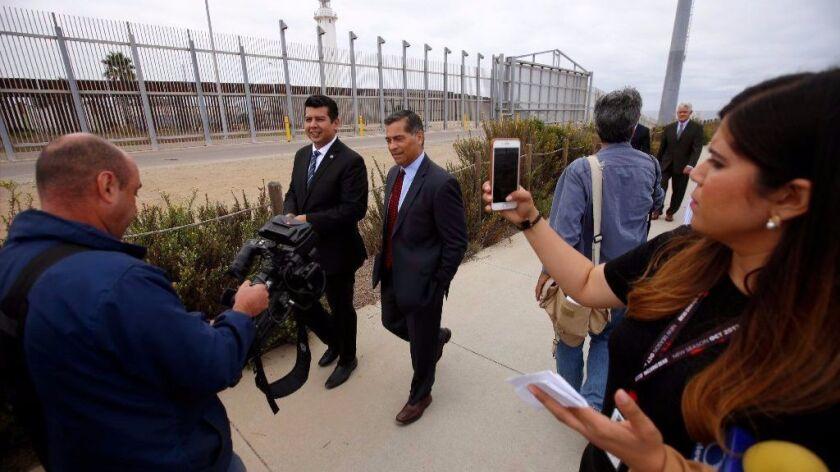 San Diego, Ca September 20, 2017: Councilmember David Alvarez , left, and Atty. Gen. Xavier Becerra, right, walk next to the border fence after a press conference in Border Field State Park in San Diego, Ca September 20, 2017.