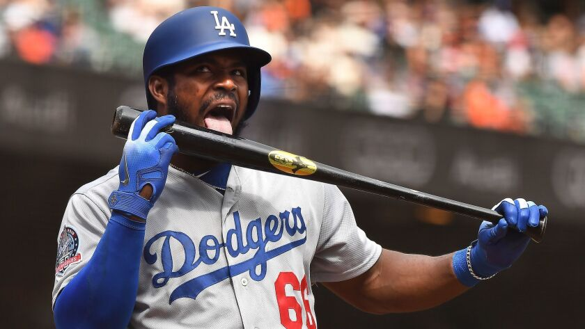 Dodgers' Yasiel Puig licks his bat before hitting a solo home run against the Giants.