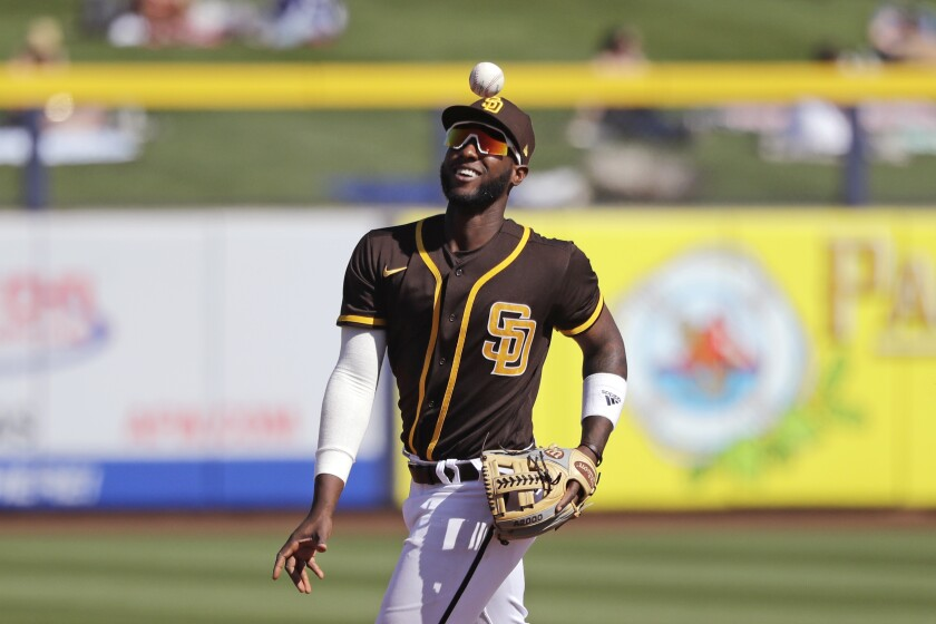 Padres second baseman Jurickson Profar smiles as he tosses a ball during a spring training game in March.