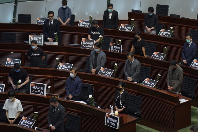 Pan-democratic legislators observe one minute of silence for the 31st anniversary of Tiananmen crackdown before a Legislative Council meeting to debate national anthem bill in Hong Kong, Thursday, June 4, 2020. On the anniversary of Tiananmen crackdown, Hong Kong continued debating a contentious law that makes it illegal to insult or abuse the Chinese national anthem. (AP Photo/Vincent Yu)