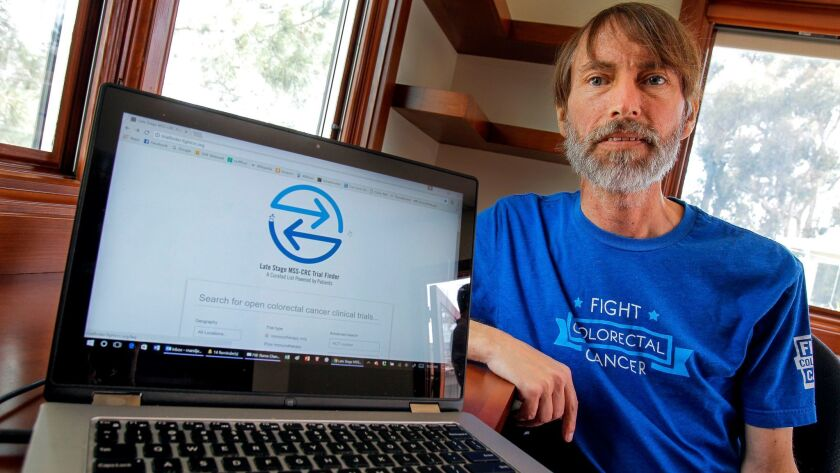 Tom Marsilje, PhD, is shown with a website he created that is a clinical trial finder for colon cancer patients. The photo was taken May 24, 2017, several months before he died of colon cancer.