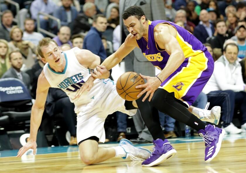 Lakers forward Larry Nance Jr. battles Charlotte center Cody Zeller for a loose ball on Dec. 20. Nance was injured during the game.