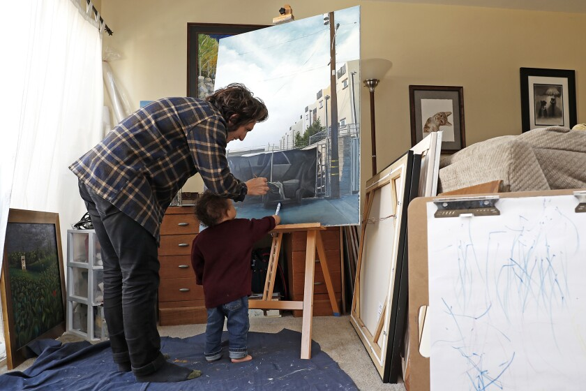 Artist Nico Sauceda spends time with his youngest son, Epic, 18 months, as they create art at their home in Huntington Beach on Thursday. Sauceda's regular job is at a custom framing store, but he's off for at least a month because of the coronavirus outbreak.