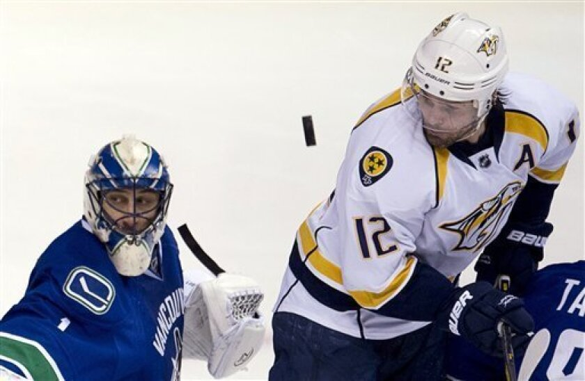 Nashville Predators center Mike Fisher (12) tries to get a shot past Vancouver Canucks goalie Roberto Luongo (1) during the second period of their NHL hockey game, Thursday, March,14, 2013, in Vancouver. (AP Photo/The Canadian Press, Jonathan Hayward)