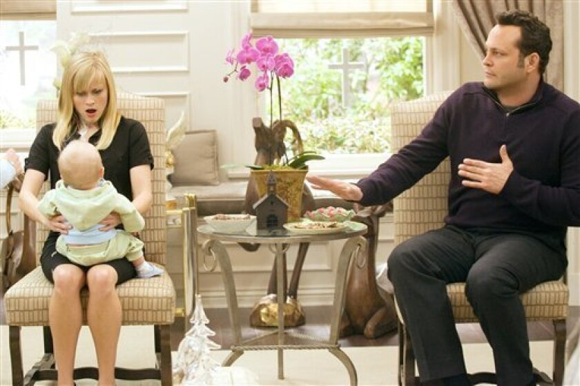 """This photo released by Warner Bros. Pictures shows Reese Witherspoon as Kate and Vince Vaughn as Brad as they discover the pitfalls of holding a baby in New Line Cinema�s romantic comedy, �Four Christmases,� distributed by Warner Bros. Pictures. Movie crowds kept up their holiday spirit as Reese Witherspoon and Vince Vaughn's comedy """"Four Christmases"""" rang up $18.2 million to lead the box office for a second-straight weekend. (AP Photo/John P. Johnson,Warner Bros. Pictures)"""