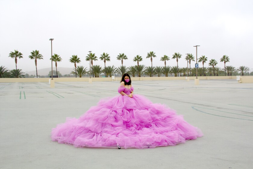 Shay Rose in her pink, 12-foot wide-social distancing dress, in an empty parking lot at the Irvine Spectrum.