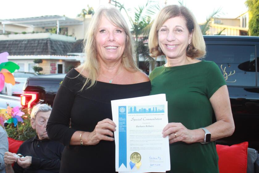Barbara Beltaire, left, receives a commendation from San Diego City Council member Barbara Bry for her years of community service.