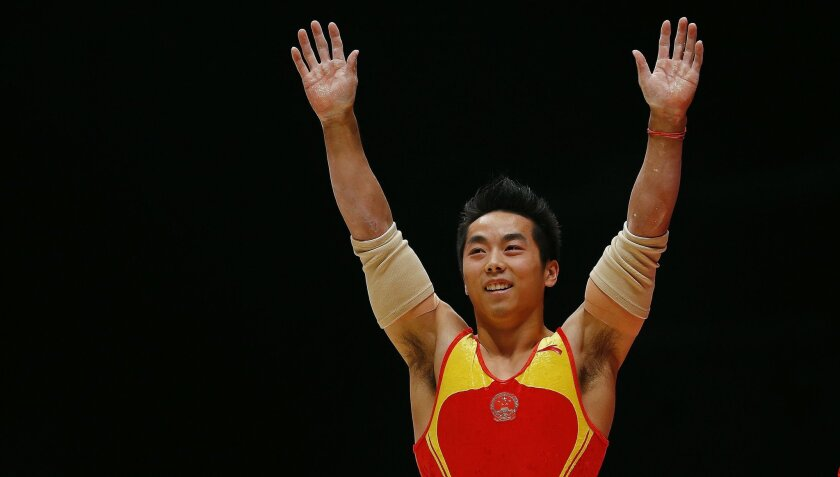 China's Hao You celebrates on the parallel bars during the men's apparatus final competition at the World Artistic Gymnastics championships at the SSE Hydro Arena in Glasgow, Scotland, Sunday, Nov. 1, 2015. (AP Photo/Matthias Schrader)