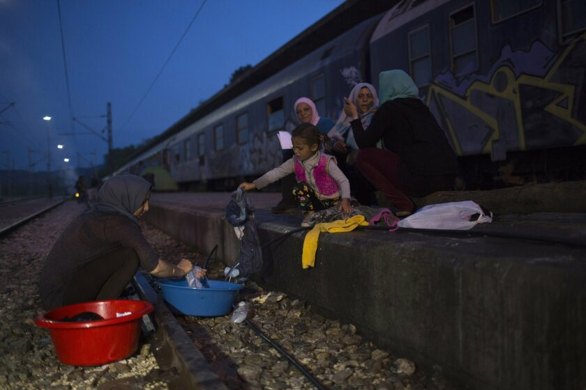 In this Tuesday, May 10, 2016 photo, a Syrian woman washing clothes on a railway tracks outside a train that refugees and migrants live in, in the sprawling refugee and migrant tent city of Idomeni, on Greece's northern border with Macedonia. (AP Photo/Petros Giannakouris)