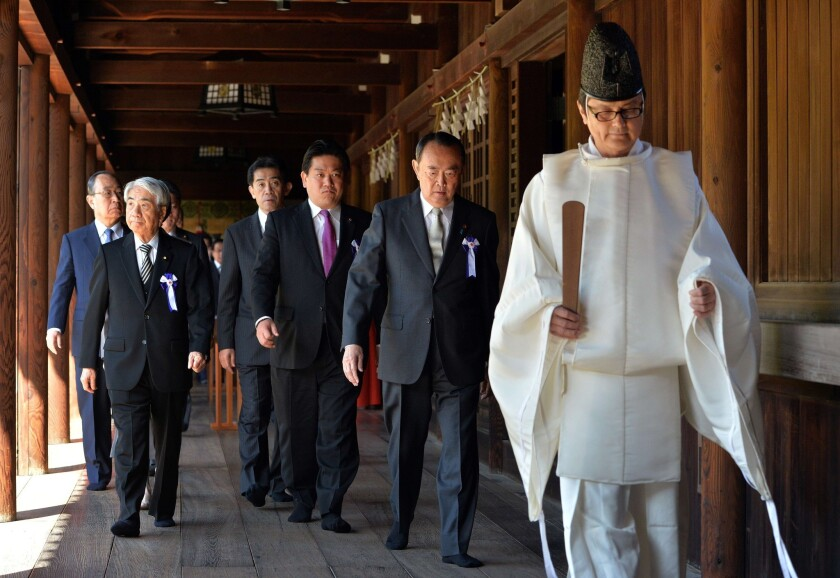Japanese lawmakers follow a Shinto priest during a visit to the controversial Yasukuni shrine in Tokyo on Tuesday to honor the country's war dead.