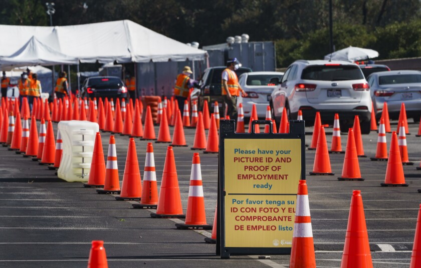 Motorists are screened as they line up for a COVID-19 vaccine appointment at the mass vaccination site at the parking lot of L.A. County Office of Education headquarters in Downey, Calif., Wednesday, Feb. 3, 2021. California continues to change up its coronavirus vaccine system with its top health officer on Tuesday suggesting revisions to who's next in line for still-scarce doses as officials put together a still-murky statewide distribution and data collection system aimed at ensuring speed and equity. (AP Photo/Damian Dovarganes)