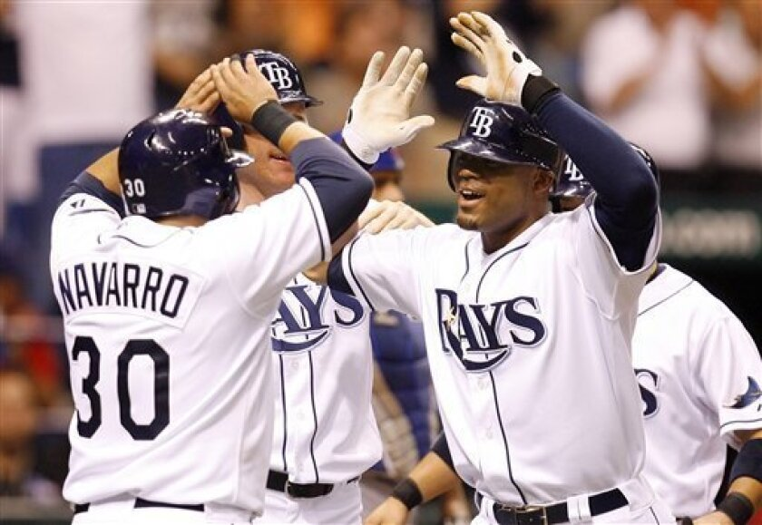 Tampa Bay Rays' Carl Crawford, right, is congratulated by teammate Dioner Navarro (30) after his grand slam home run in the seventh inning of a baseball game against the Chicago Cubs Thursday, June 19, 2008, in St. Petersburg, Fla. (AP Photo/Mike Carlson)