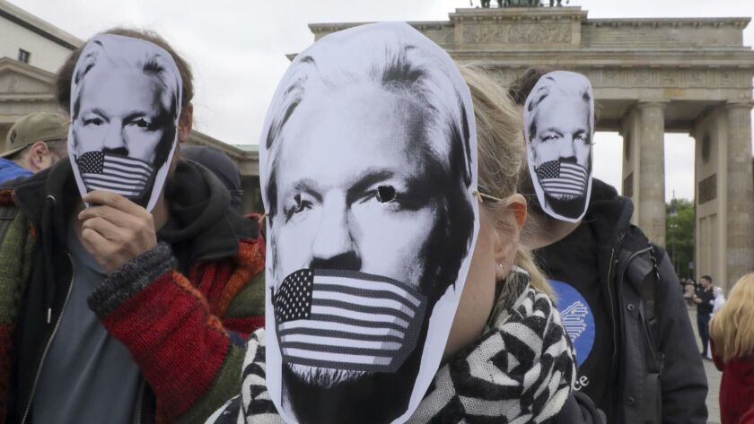 People wear paper masks to protest against a possible extradition of WikiLeaks founder Julian Assang
