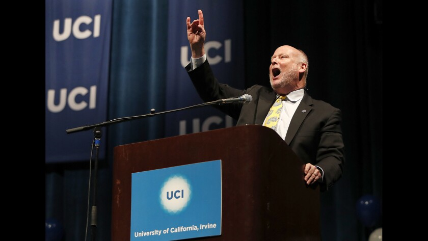 """UC Irvine Chancellor Howard Gillman gives the """"zot, zot, zot"""" hand signal during the 2019 College Signing Day rally in May at the university's Bren Events Center."""