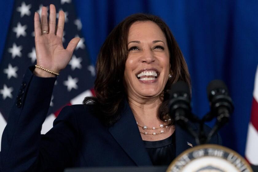 Vice President Kamala Harris waves from a lectern