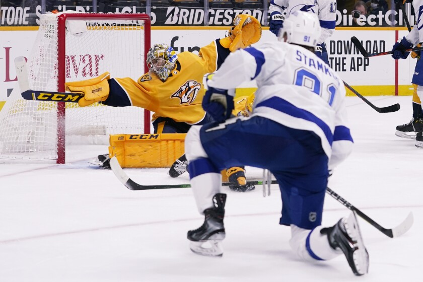 Nashville Predators goaltender Juuse Saros (74) reaches for a shot by Tampa Bay Lightning center Steven Stamkos (91) but can't stop the puck as Stamkos scores in the third period of an NHL hockey game Tuesday, Feb. 9, 2021, in Nashville, Tenn. (AP Photo/Mark Humphrey)