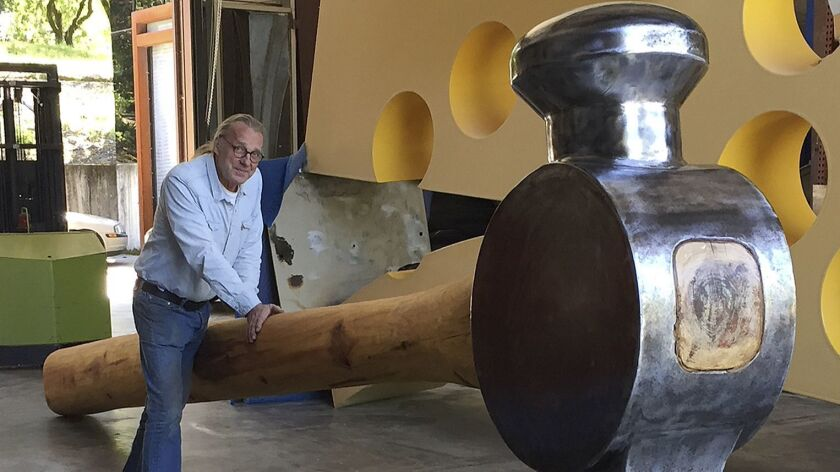 Artist Doug Unkrey is seen in 2017 with the giant hammer he created at his studio in Geyserville, Calif.