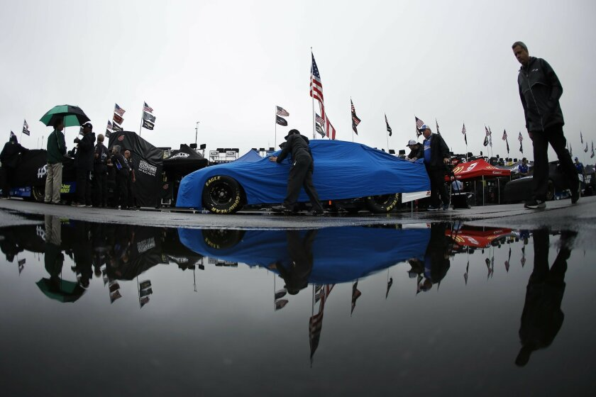 Crew members push the car of Chris Buescher through the garage area to be inspected for Sunday's NASCAR Sprint Cup Series auto race, Friday, June 3, 2016, in Long Pond, Pa. (AP Photo/Matt Slocum)