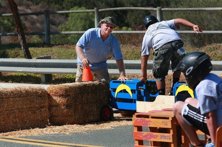 Terry Hanvey helps driver Lyzaiah Wright, 11, climb out of his car after it comes to a stop in the hay bales at the bottom of the course.