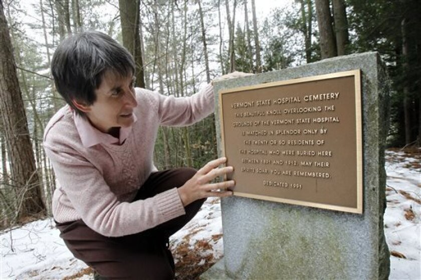In this Thursday, March 28, 2013 photo, Rep. Anne Donahue looks at a memorial stone at the site of a Vermont State Hospital cemetery in Waterbury, Vt. Vermont mental health advocates are trying to decide what to do with the abandoned cemetery near the former State Hospital, which was forced to move