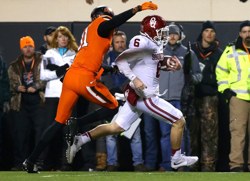 Oklahoma's Baker Mayfield rushes past Oklahoma State's Tre Flowers on Saturday.