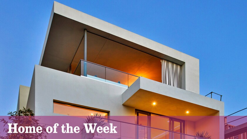 The contemporary-style residence has a top-level lounge and a side yard with a small theater.