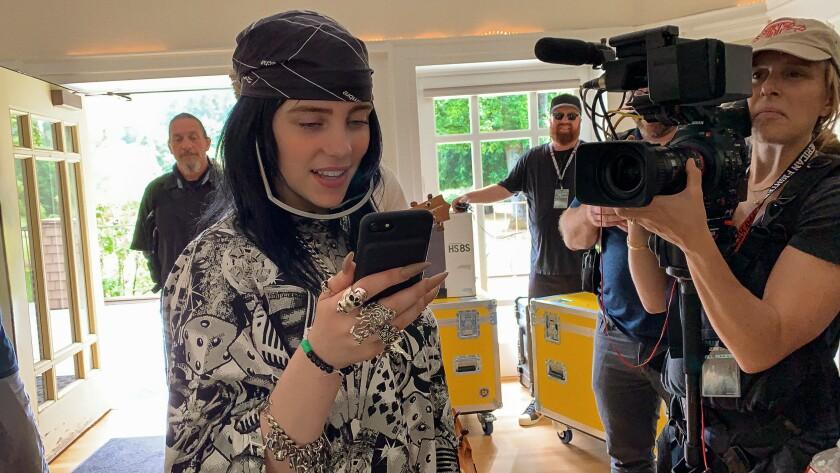 Singer/songwriter Billie Eilish checks her phone during a video shoot.