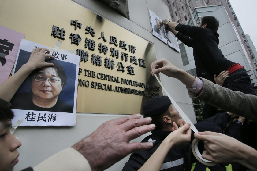 FILE - In this Jan. 3, 2016, file photo, protesters try to stick photos of missing booksellers, one of which shows Gui Minhai at left, during a protest outside the Liaison of the Central People's Government in Hong Kong. Angela Gui, the daughter of a Hong Kong-based publisher Gui Minhai, believed abducted by Chinese authorities eight months ago, appeared Tuesday, May 24, 2016, before a U.S. congressional commission urging Washington's help to win his release. (AP Photo/Vincent Yu, File)