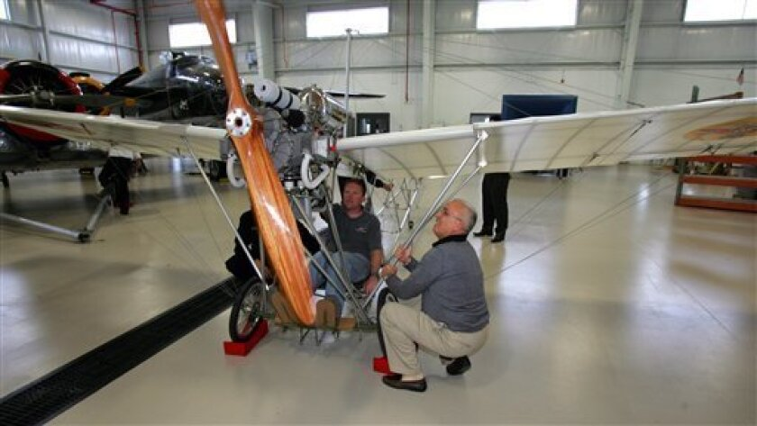 In this Sept. 28, 2009 photo, Brazilian industrialist Fernando de Arruda Botelho, right, and pilot Chris Palmer inspect a rare replica of the Demoiselle, a 1908 airplane, at the Champaign Aviation Museum in Urbana, Ohio. Botelho had the replica of the Demoiselle, designed by Brazilian air pioneer Alberto Santos Dumont, built. The Demoiselle has gone on exhibit in Wright brothers country and is expected to stay for at least a year, the longest it will have ever been in the United States. (AP Photo/Skip Peterson)