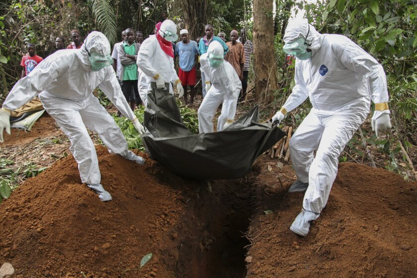 Liberian nurses bury the body of an Ebola victim on the outskirts of Monrovia.