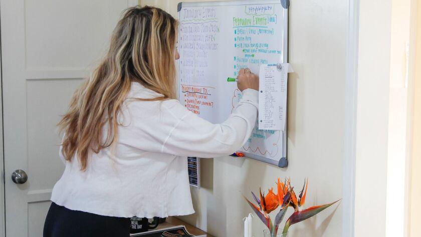 Moishe House resident Miranda Kalman fills out an events calendar at her home on Thursday in Oceanside.