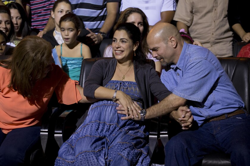 Gerardo Hernandez, a Cuban spy recently freed from a U.S. prison, touches the belly of his pregnant wife, Adriana Perez, during a concert in Havana on Dec. 20. They are expecting a girl.