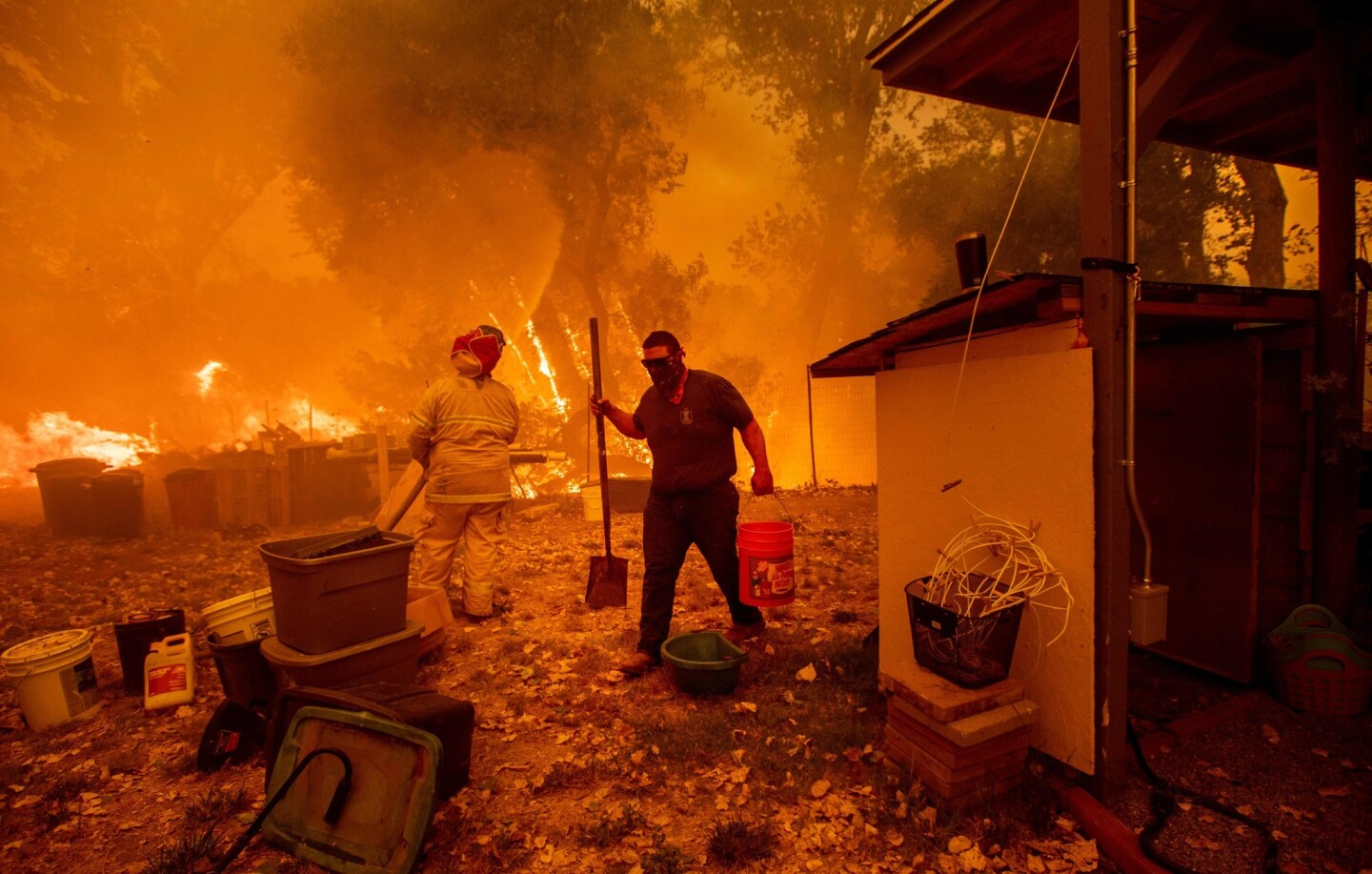 Resident Lane Lawder carries a water bucket while fighting to save his home from the Ranch fire burning along New Long Valley Road near Clearlake Oaks.