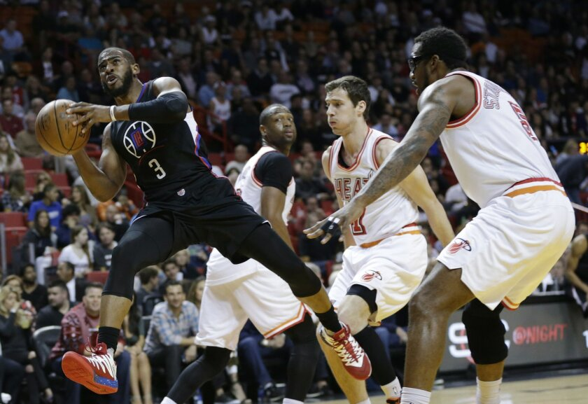 Los Angeles Clippers guard Chris Paul (3) drives to the basket past Miami Heat guard Goran Dragic (7) and forward Amare Stoudemire, right, during the first half of an NBA basketball game, Sunday, Feb. 7, 2016, in Miami. (AP Photo/Lynne Sladky)