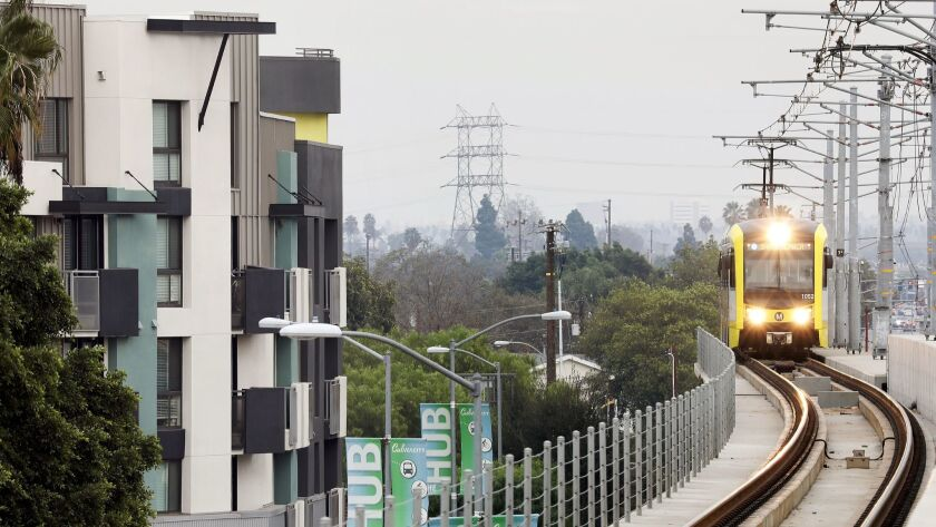 A Metro train passes by apartments in Culver City.